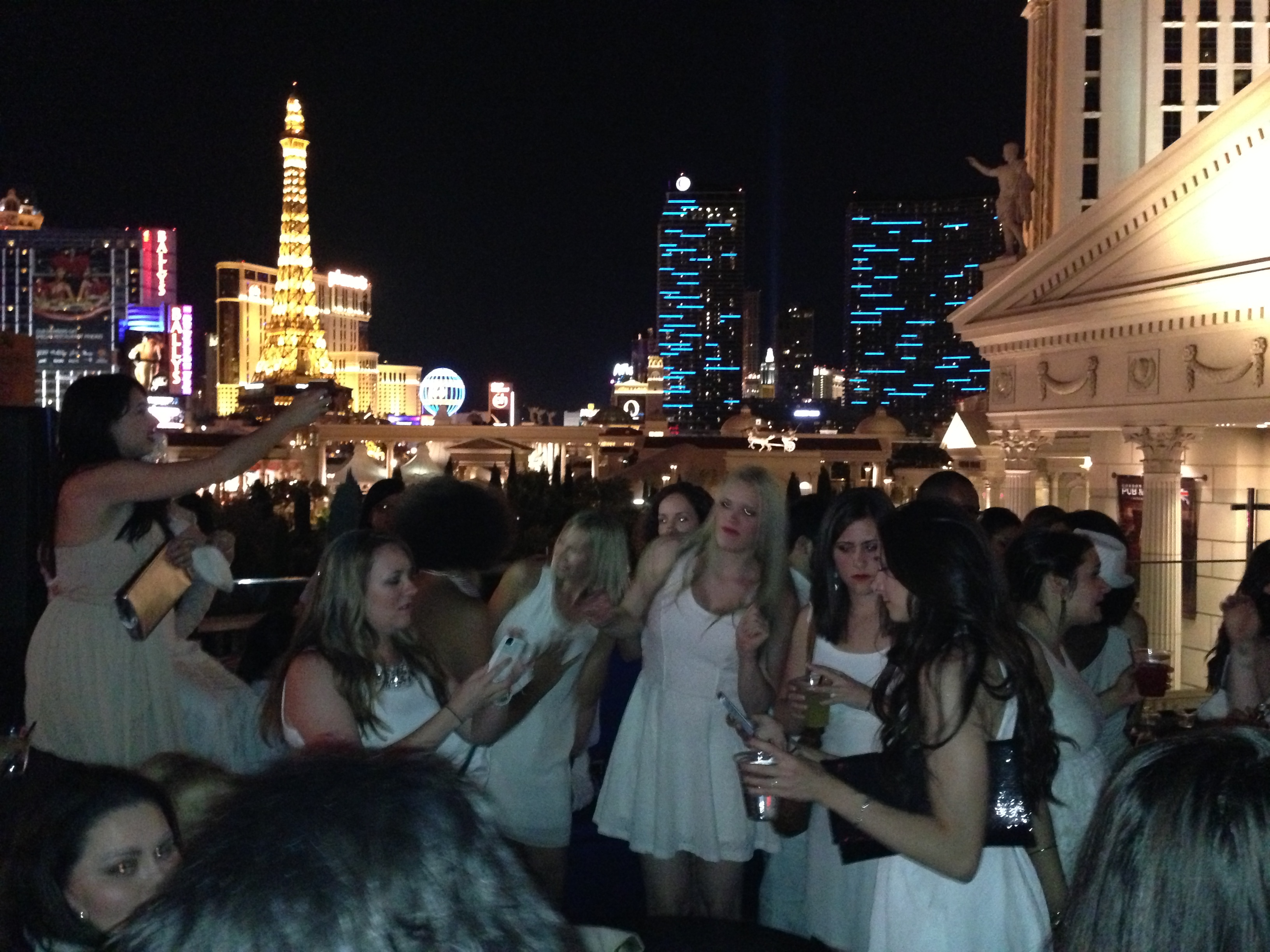 Rooftop view of white clad party people (us) and skyline.