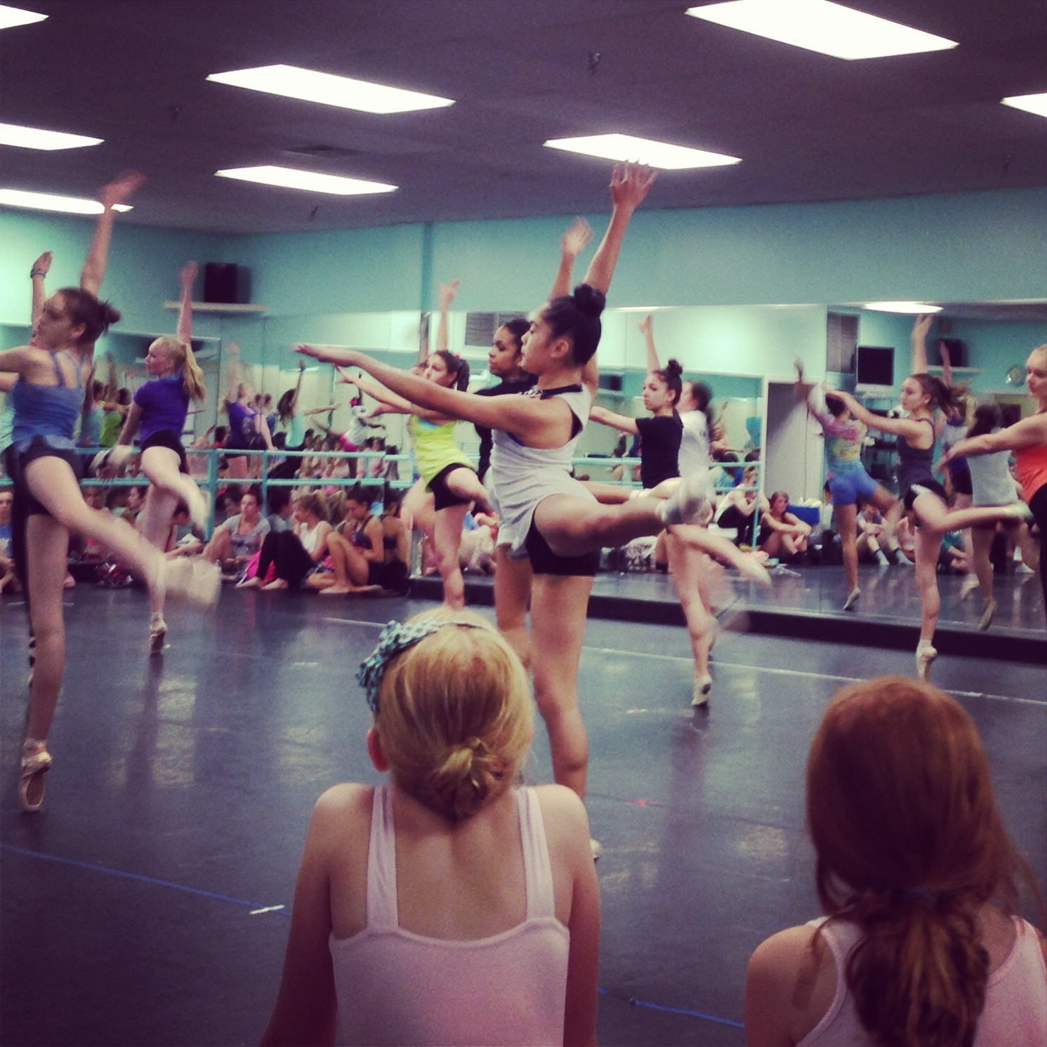 """big girls"" running their pointe pieces as pre-ballet girls watch on."